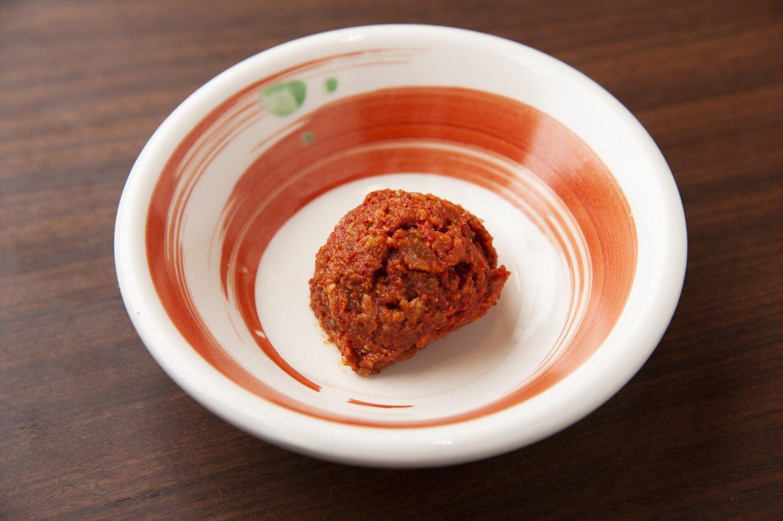 〈 ピリ辛ポイント 〉数種類の味噌と肉、野菜、スパイスを混ぜ込んだ辛味玉。少しずつスープに溶かして味の変化を楽しみたい。