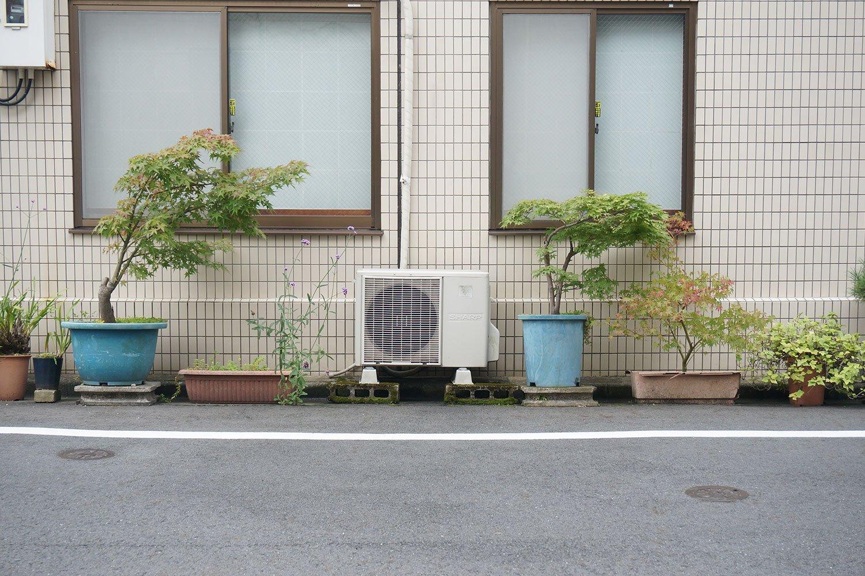 「室外機がセンター」みたいなフォーメーションの植木鉢の配置。室外機を中心に、左右のバランスを考えて配置したのかもしれない。