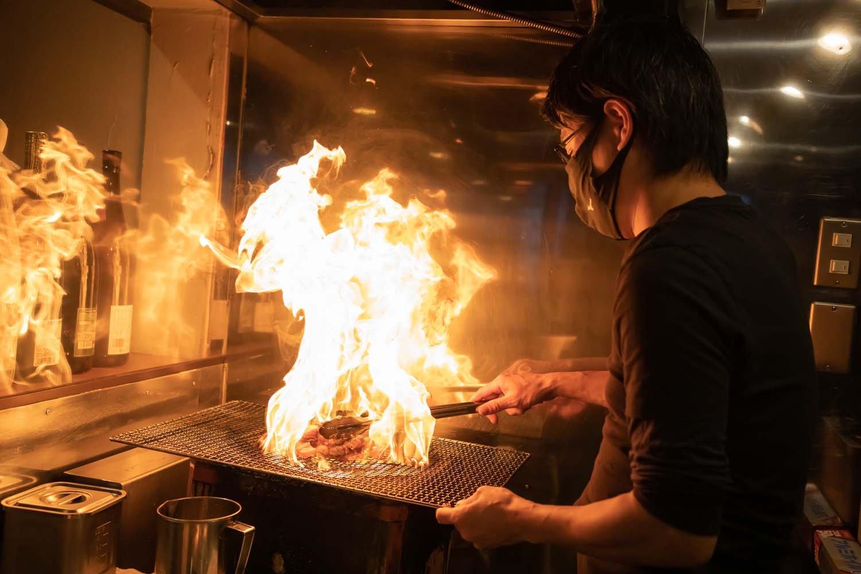 油を注ぐと一気に炎が上がり、煙が立ち上る。熟練の技が必須の調理法だ。