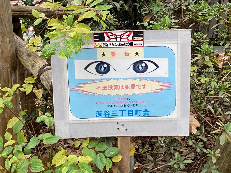 渋谷の植え込みにあった立て札。目のイラストと隈取ステッカーの合わせ技である(渋谷・2020年)