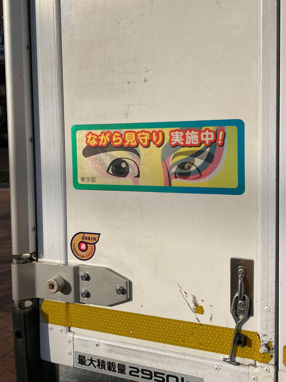 「動く防犯の眼」のバリエーションとして、仕事をしながらの「ながら見守り」の取り組みも進められている。コンビニの配送トラックの後部に貼られた、レンチキュラー加工がされた「普通の目」と「にらむ隈取」のステッカー(府中・2021年)