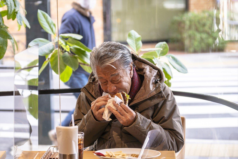 ハンバーガーをガブり。「僕の好きな、たまごかけごはんよりうまいよ」。