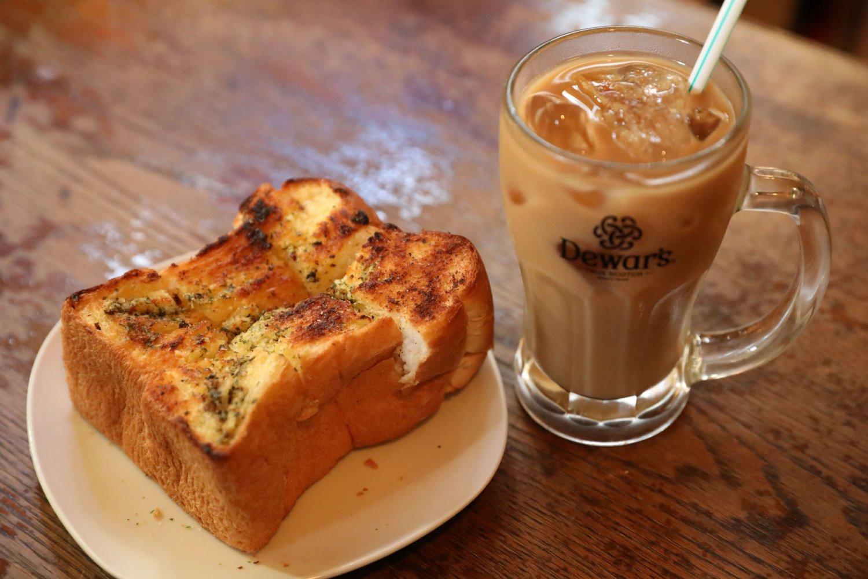 取材時は当時もよく頼んでいたガーリックトースト200円やアイスカフェオレ300円(S)を注文。安さも美味しさも当時のまま。