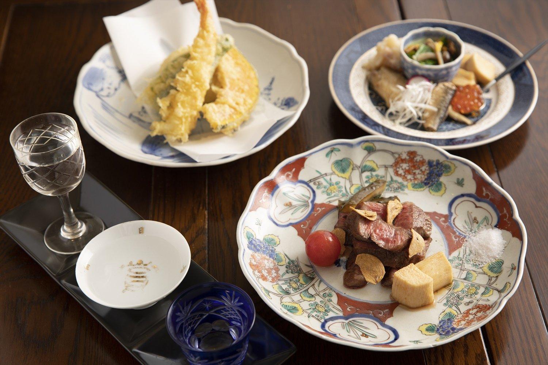 古伊万里などアンティークの器が美しい。黒毛和牛のみすじのステーキは1g18円で注文は100gから。天然海老・野菜天の3種盛り590円。自家製イクラしょうゆ漬けなど八寸プレート1000円。日本酒飲み比べセット3杯で880円~。