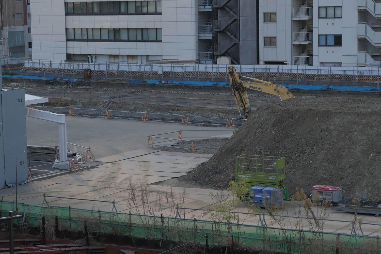 """高輪ゲートウェイ駅改札外から""""高輪築堤""""をみる。ショベルカーのアーム部分にうっすらとグレー色の石垣が見えるはず……。2021年2月撮影。"""