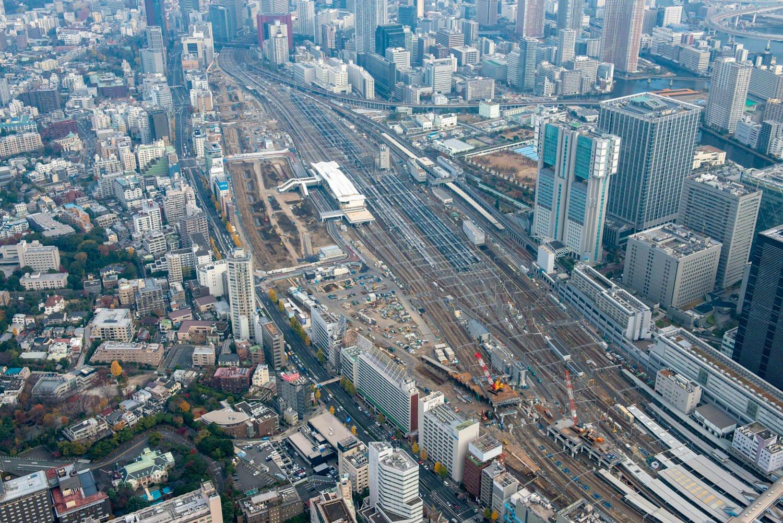 """品川駅から高輪ゲートウェイ駅方向をみる。""""高輪築堤""""は一直線に並ぶビル群の右脇に存在している。堀状になっているのが築堤発掘現場。"""