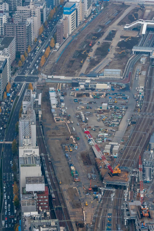 品川駅は手前。京急電車の右隣に築堤が埋まっている。赤白色の大型クレーンの近くでも発掘調査をしている。