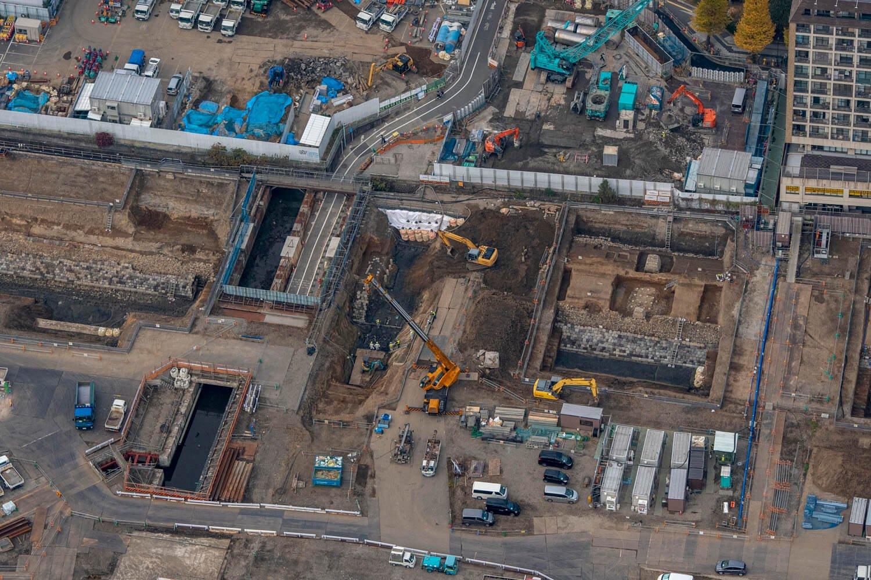 """""""高輪橋架道橋""""と築堤の位置関係が一目瞭然。山手線の橋台のすぐ隣には築堤が発掘されている。この部分は""""第二東西連絡道路""""という新たなガードが造られる予定。そのためなのか、一部の石垣は撤去されている模様だ。発掘調査が終了して工事に入ったのだろうか。"""