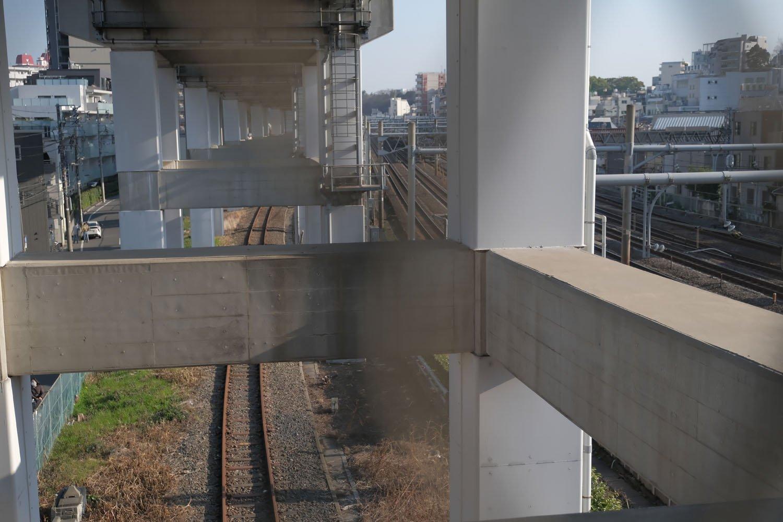 跨線橋の網目から王子駅方向を見やると新幹線高架下に北王子線の錆びた線路がある。