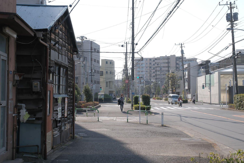 軽バンとスクーターが走る道路が須賀線の跡。左の古い家屋は鉄道があった時代を知っているのだろうか。