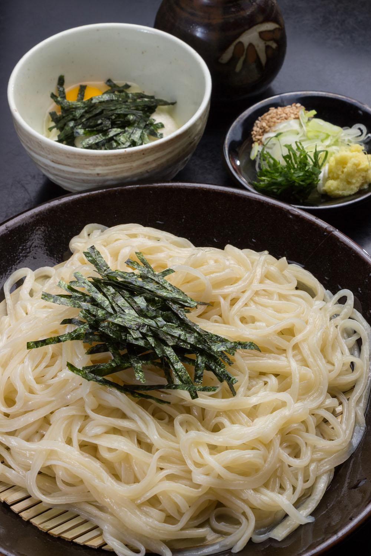 とろろうどん1250円で透明感がありやや平打ち、やわらかな粘りがある麺の喉ごしを堪能。稲庭の麺に近い食感。