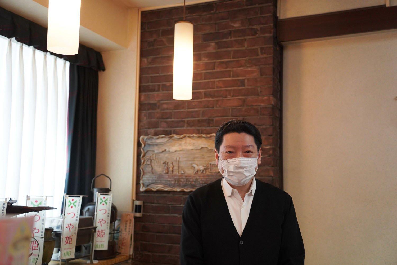 店主の木田浩一朗さん。1階の壁には銀座煉瓦街で使われていた煉瓦が飾られている。