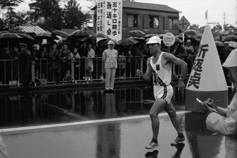 府中市の50㎞競歩折り返し点にて。府中市はマラソン折り返し点も誘致したが国立競技場トラックも回るため数100m足りずに調布市に決定。この時の国際審判員・津田直彦氏は海外から競歩連続写真を取り寄せ研究した。(写真:フォート・キシモト)