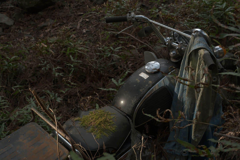 先ほどの分岐道に遺棄されたバイク。苔むしてきているようだ。