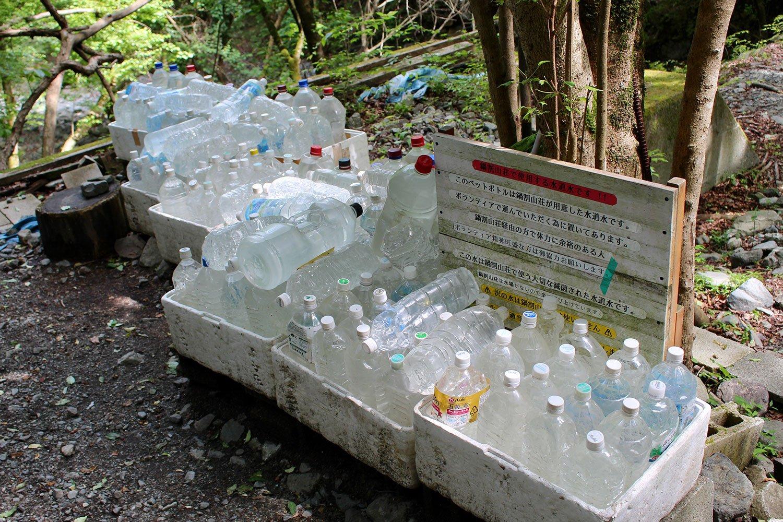 登山口に置かれたペットボトルの水。登山者の多くがボランティアで小屋へ運んでくれる。