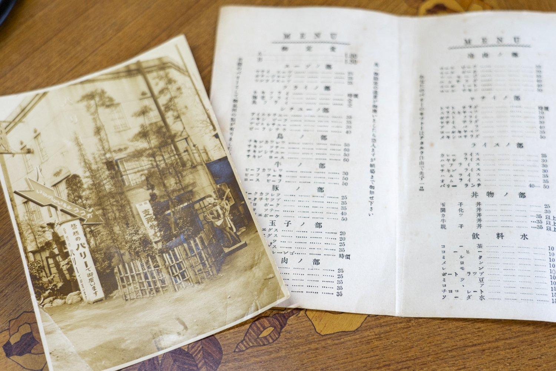 創業当時の写真とメニュー。「オムライス 35銭」の文字が見える。