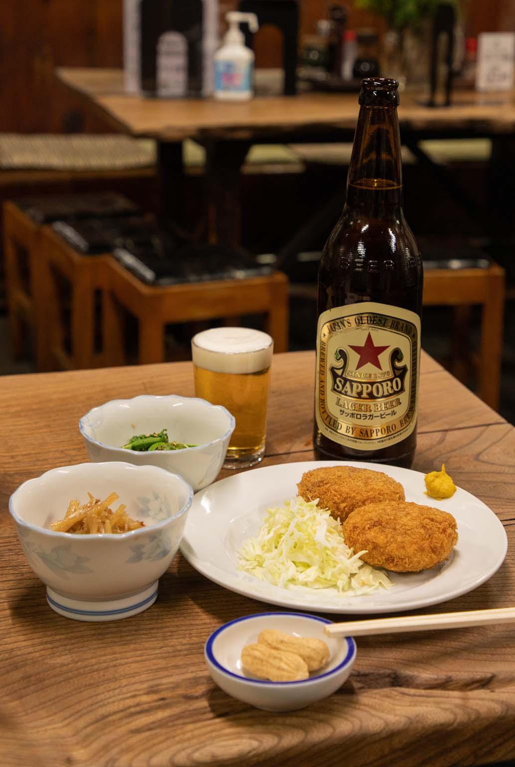 カレーコロッケは2つで360円、うどのキンピラ320円(手前)こごみ340円(奥)サッポロラガービール1本540円。