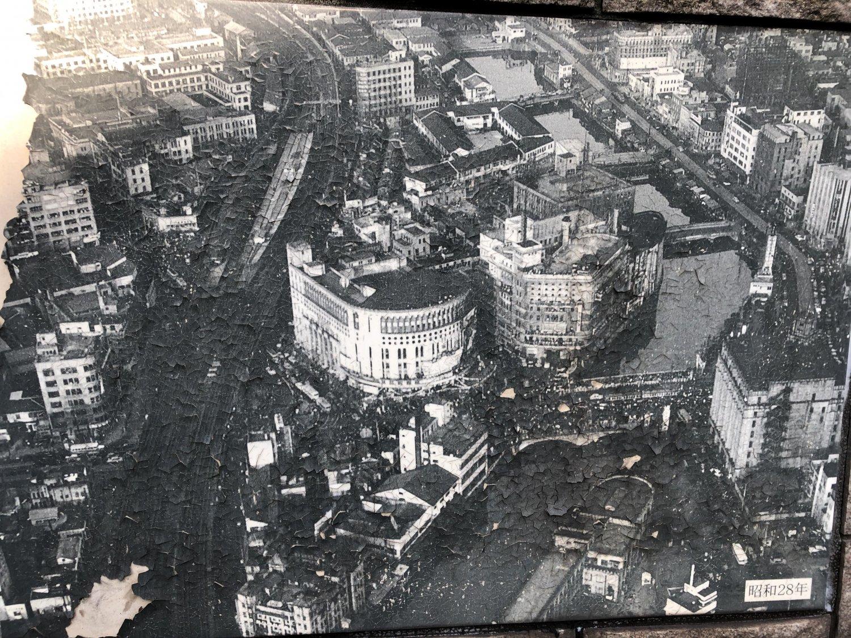 昭和28年の有楽町。数寄屋橋が架かる外堀は、現在、首都高速の高架と西銀座デパートに。また、外堀沿いの朝日新聞と日劇は、有楽町マリオンになっている。