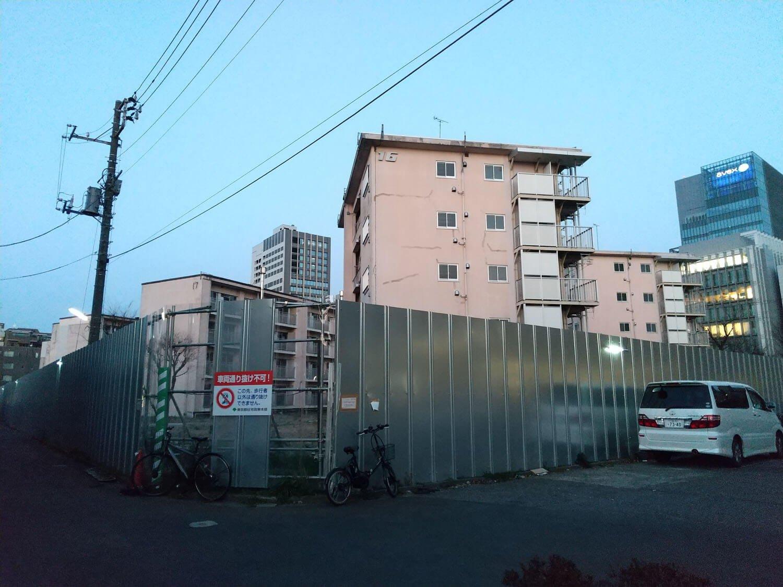 廃墟となった団地群が目の前に広がる。大都会にぽつんと取り残された空間。一部のフェンスは透けて内部が見える。