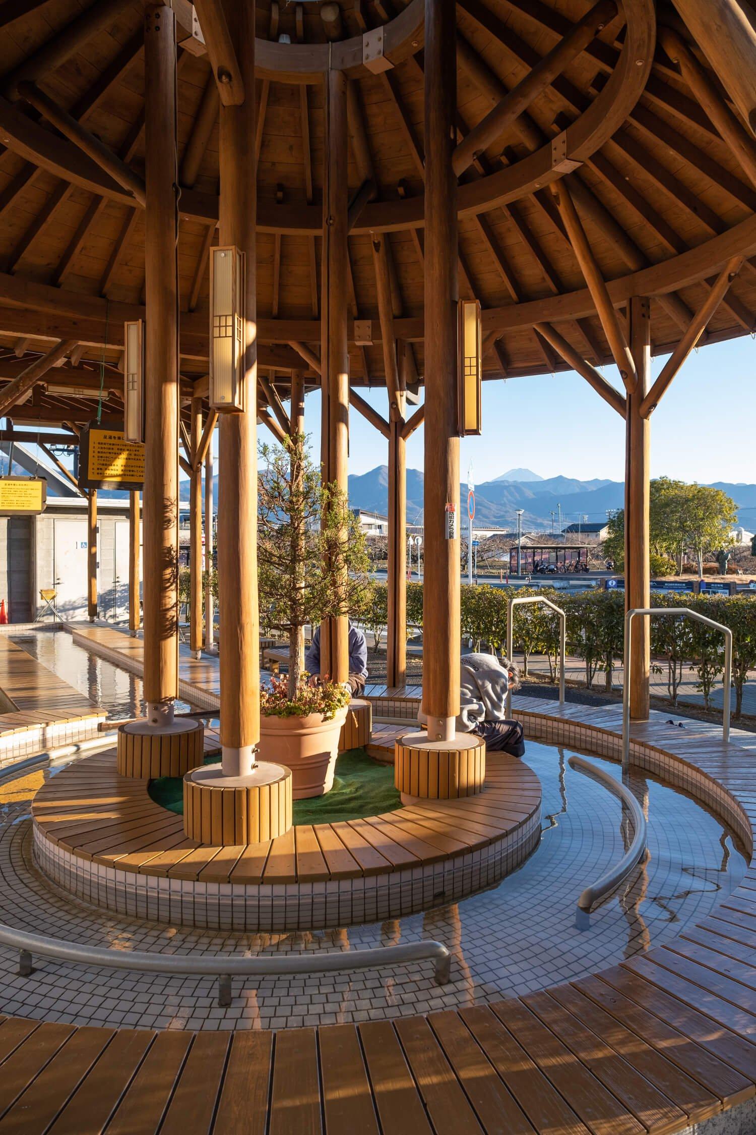春日居足湯施設からは御坂(みさか)山塊の先に頭をのぞかせる富士山の姿もチラリ。