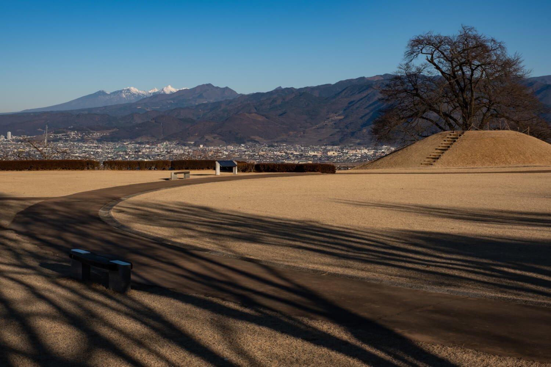 直径 23 mの盃塚古墳の先には八ヶ岳(左奥)が鎮座している。