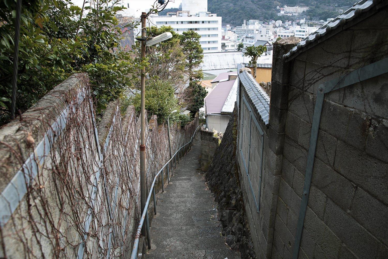 民家を縫うように延びる階段坂。一体、その先はどこへ続くのか。