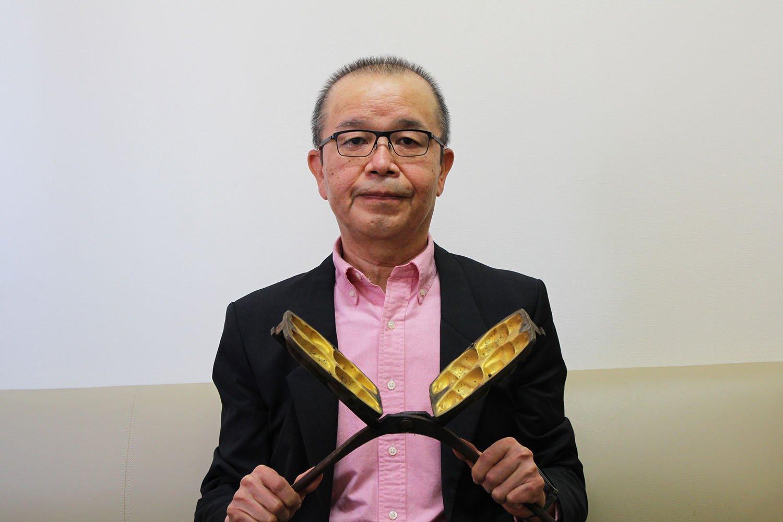取締役専務の山田満さん。手にしているのは昔の手焼きの人形焼の型。