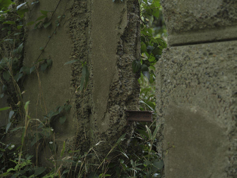 門柱の一部が壊れてトロッコレールが顔を出している。