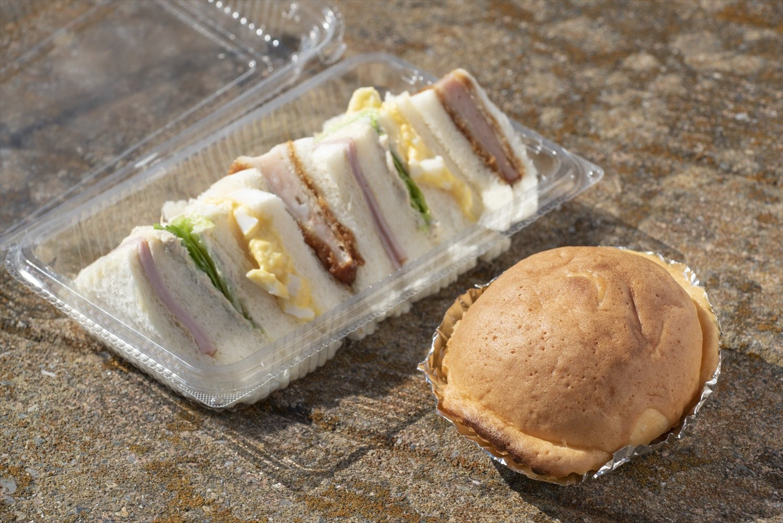 カステラ生地にカスタードクリーム入りの菓子パンUFO150円とサンドウイッチ350円。