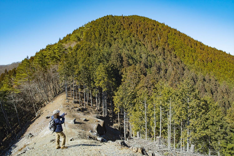 視界が開けた送電線跡地から、露天採掘地や里の風景が見渡せる。