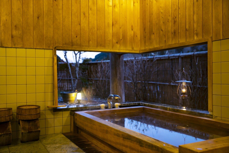 ヒノキ風呂。石灰質の井戸水を薪で沸かし、肌になじむよう。空と山を眺められる。