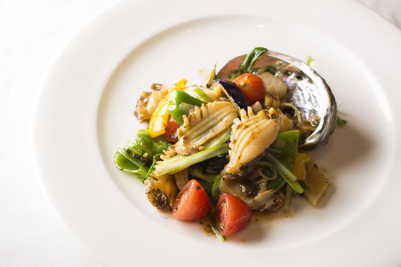 活蝦夷アワビと旬野菜の肝醤ソース炒め2700円。アワビは一皿に丸々1個。万願寺唐辛子、マコモタケなど旬野菜が彩りとアクセントを加える。