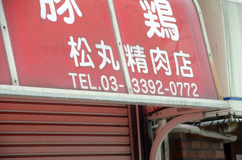 テントに注目して見ると……左端に「松丸精肉店」という表記が!