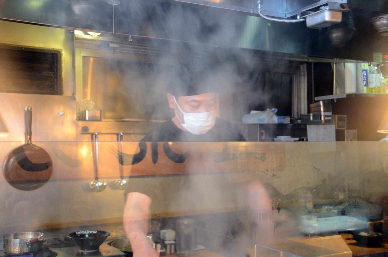 厨房内でラーメン作りに励む小島さん。もうもうと湧く湯気が食欲をそそる。