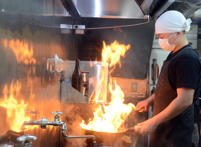 特製十八番の味を決めるニンニク炒めはオーダーと同時に調理開始。舞い上がる炎とともに中華鍋からは食欲をそそるいい香りが!