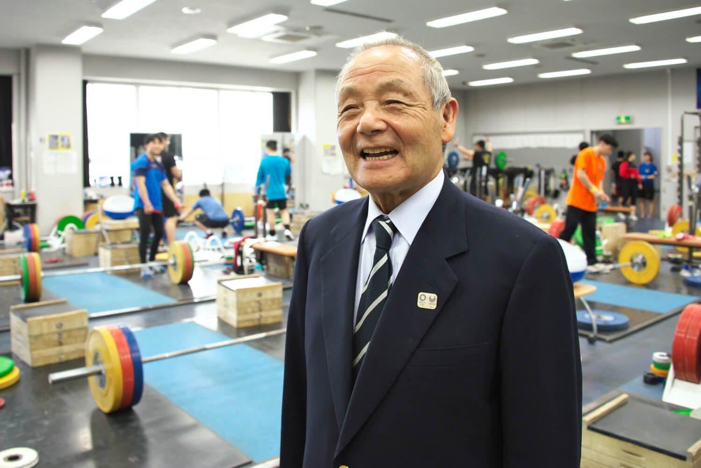 第一期生の三宅義信さんは体育学校校長も経験し、校内の体育館や植栽を整備した。現在は写真の東京国際大学ウエイトリフティング部監督。「生涯好きな道で幸せです」。