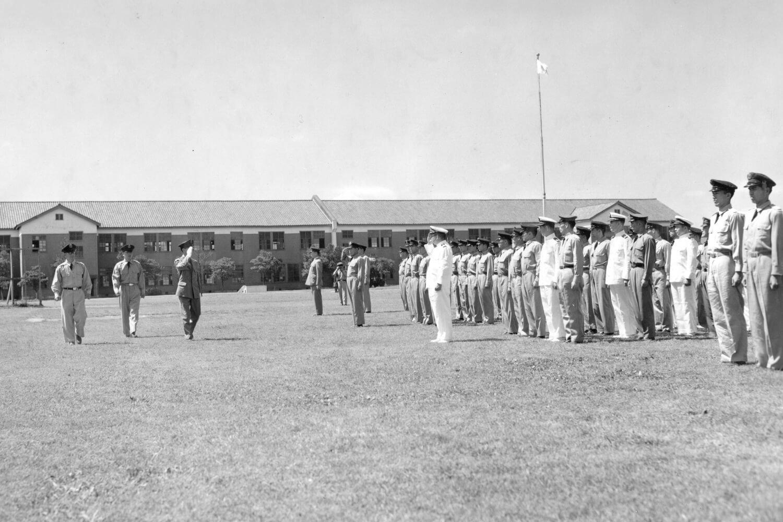 体育学校は1961年朝霞駐屯地に創設された。陸・海・空自衛隊の共同機関なので、選手はいずれかに所属する。写真の白い制服は海上自衛隊で、奥の昭和16年(1941)築の旧陸軍予科士官学校が校舎だった。「古くて雨漏りするし、夏は暑くて眠れない」と三宅さん。「でも自衛隊の皆さんのご理解とご協力でオリンピック出場は成功をおさめました」。(写真提供:自衛隊体育学校)。