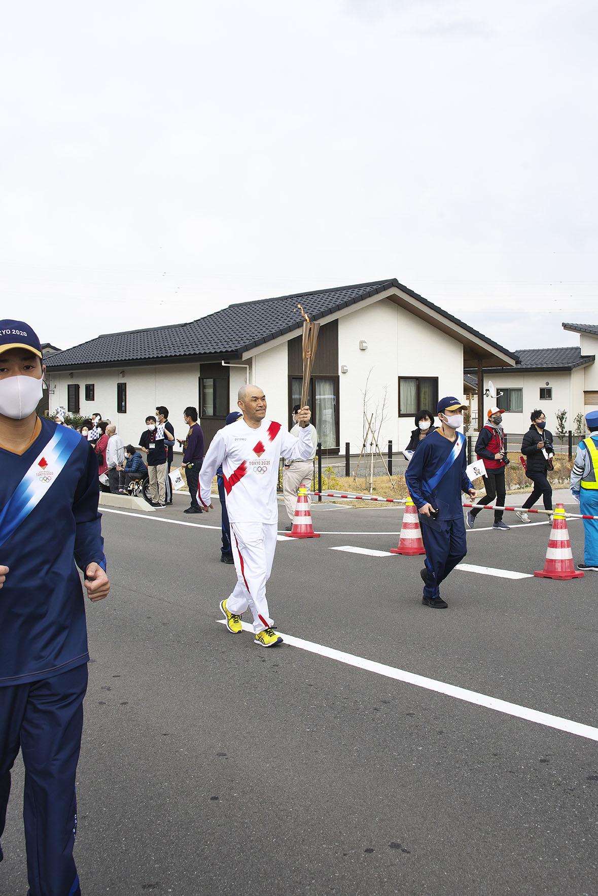 災害公営住宅前を走る聖火ランナー。