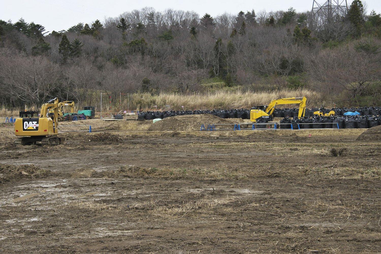 除染作業風景。表土をフレコンバッグに詰めては積み上げる果てしない作業をもう10年も続けている。