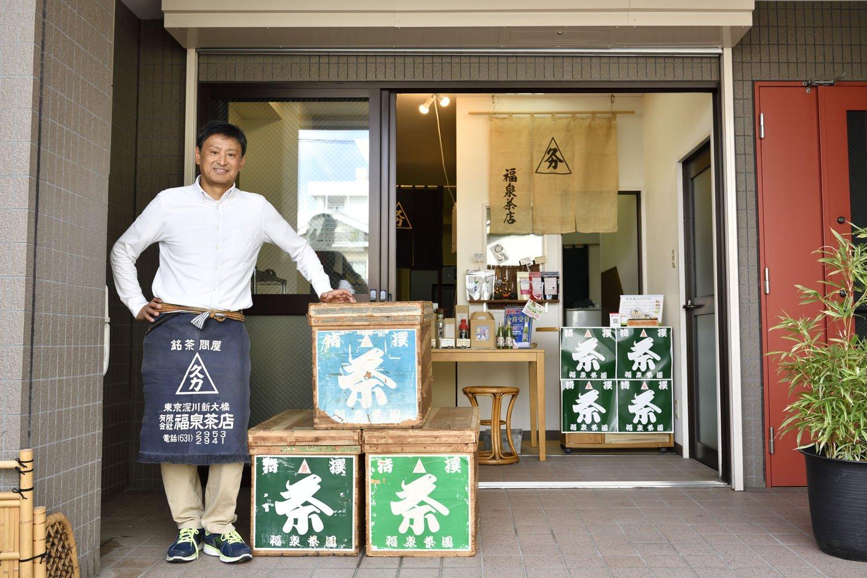 販売している年代物の茶箱と菊地さん。