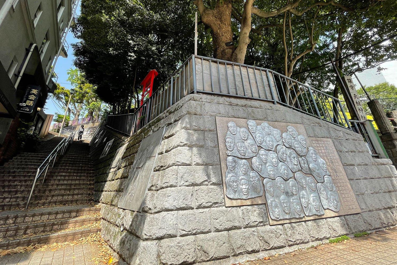 JR大森駅西口目の前の神明山天祖神社の下には、文士たちのレリーフが刻まれる。坂を登れば、かつての馬込文士村へ。