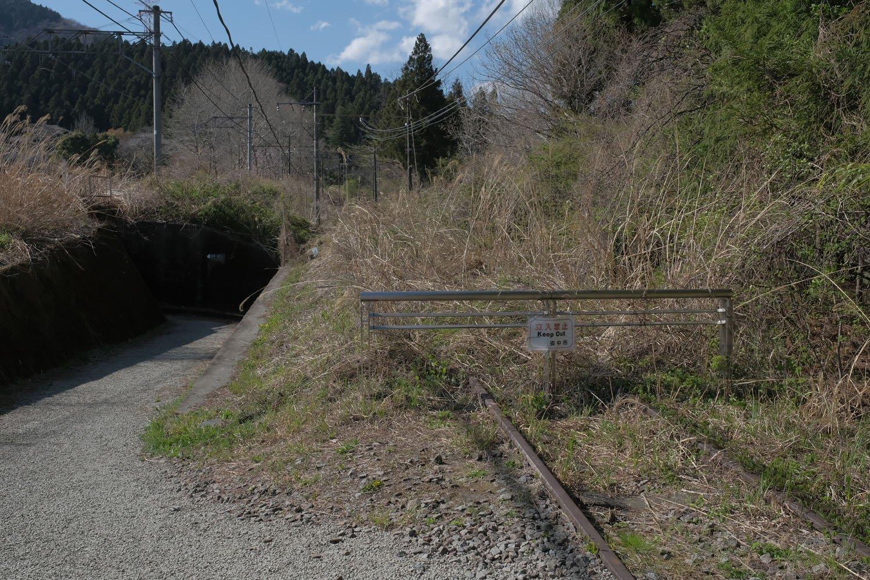 """舗装されていた道は突如として草むした線路へと変わる。この先の朽ち具合こそが""""廃もの""""にうってつけなのだが立入禁止である。潔く諦め、時々開催される廃線ウォークに参加しよう。"""