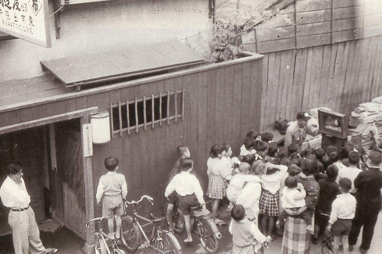 1954年の人形町の紙芝居の様子。おんぶされている柏原さんの姿も。(写真提供=柏原寛司さん)