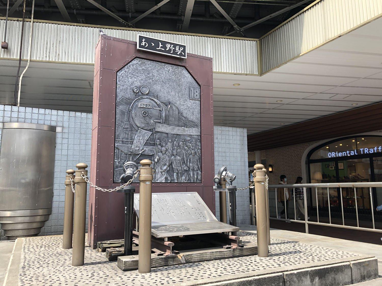 上野広小路口にある「あゝ上野駅歌碑」のレリーフには、上野駅に降り立つ「金の卵」たちが描かれている。