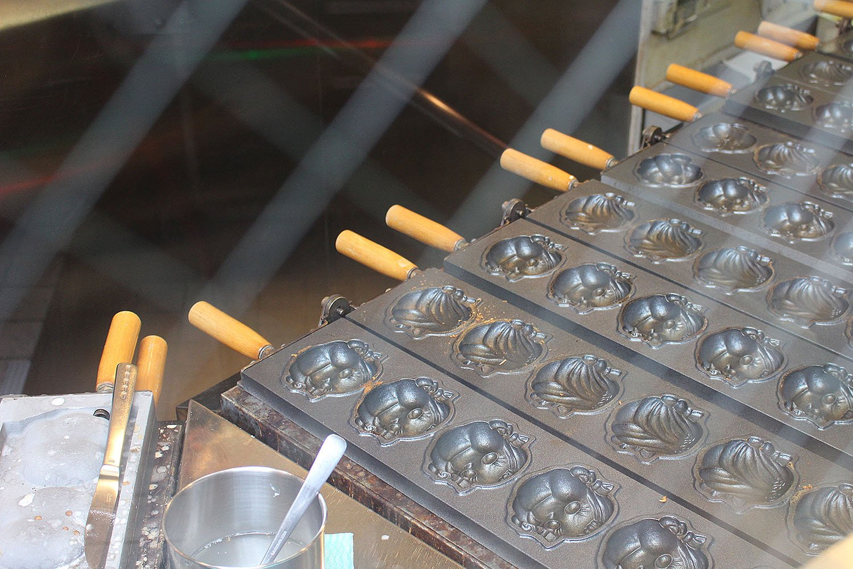 神楽坂通りからガラス越しにペコちゃん焼を焼く様子が見える。