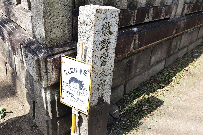 牧野富太郎博士の墓の方向を示す石碑。横に立つ手描きの看板が味わい深い。