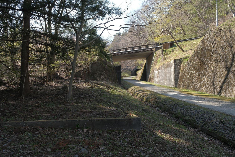 旧国道が渡る跨線橋と旧線跡。傍らには詰所の基礎が残っていた。アプト式時代の走行写真は、この跨線橋上から撮られたものをよく見かける。今もアプト式が現役だったとしたら、間違いなくお手軽撮影地として賑わっていたに違いない。