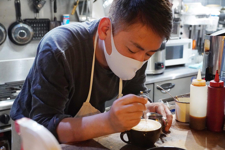 器用にラテアートを描く、店長の上田さん。