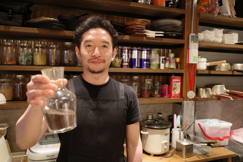 お気に入りのマスタードシードを手に持つ店主の小田さん。トークと気配りが上手な小田さんの人柄に惹かれて通う常連さんも多い。
