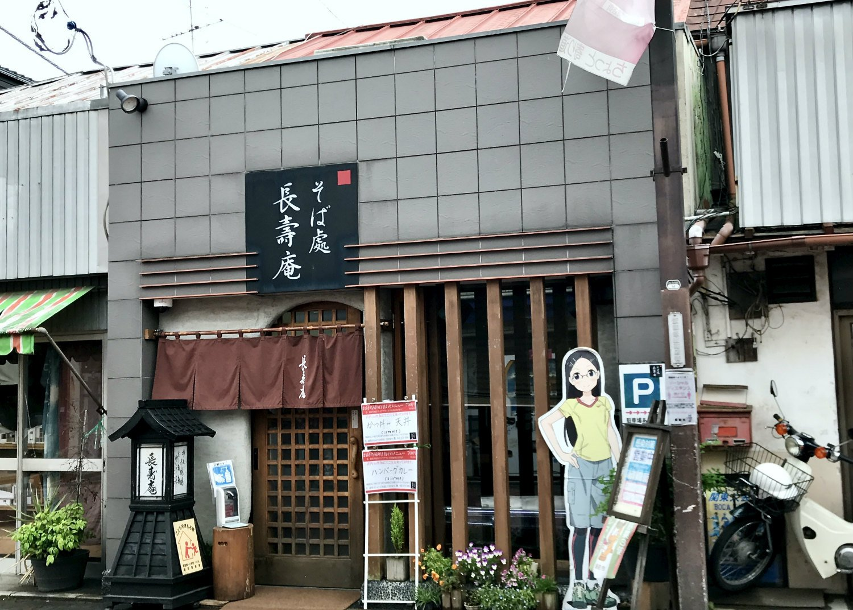 店舗向かって右に立つパネルは、飯能が舞台のアニメ『ヤマノススメ』のキャラクター。『長寿庵』もチラッと登場するらしい。